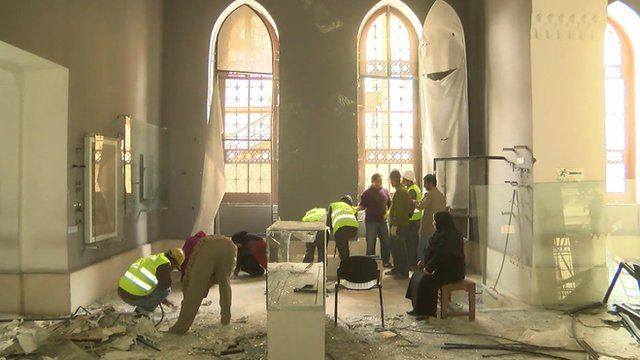 Workers cleaning up debris in museum