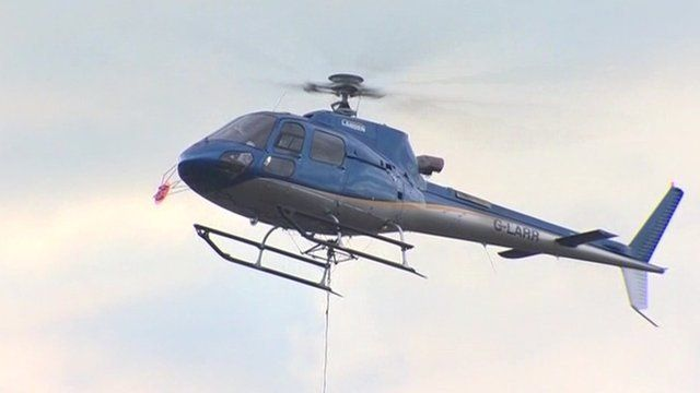 Helicopter carries large bag of fine slate
