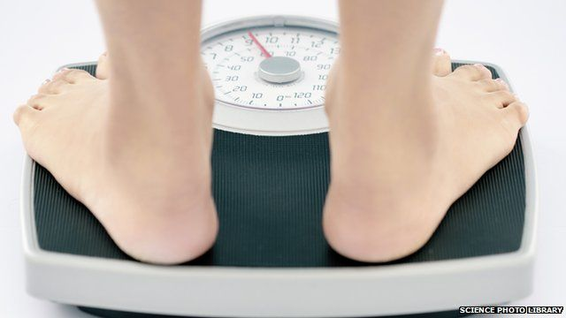 A young slim woman weighs herself on bathroom scales
