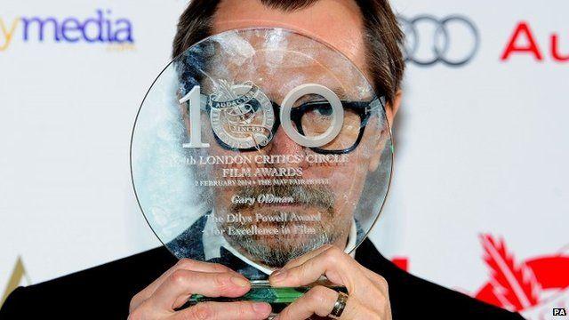 Gary Oldman hiding face with award