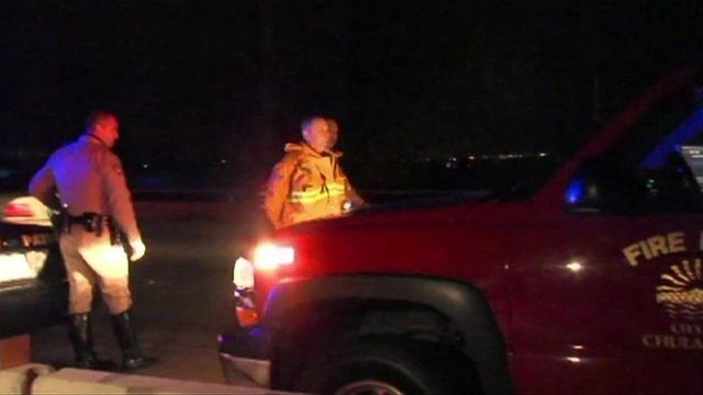 A firefighter is handcuffed by Highway Patrol officers