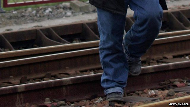 An immigrant crosses railway tracks in Calais, France