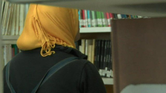 A woman in a headscarf looks at books