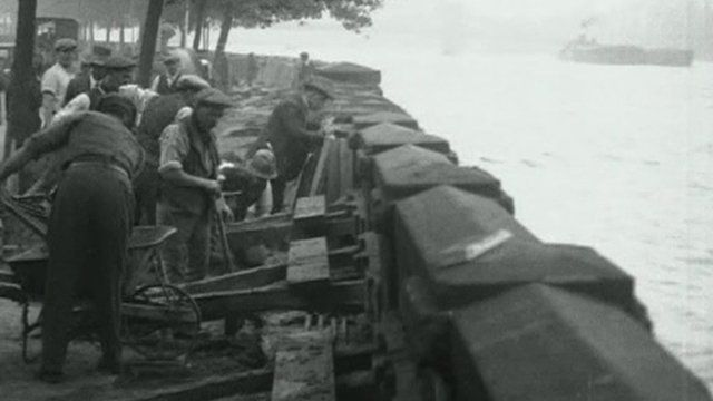 Workmen putting sandbags on the Thames in 1928