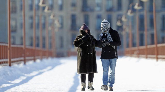 People walk along a bridge over the Mississippi River in Minneapolis