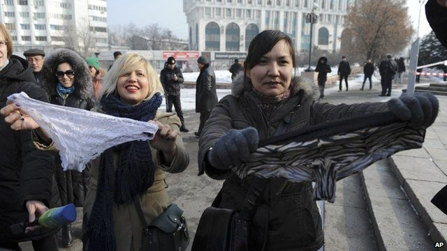 Women hold synthetic lingerie