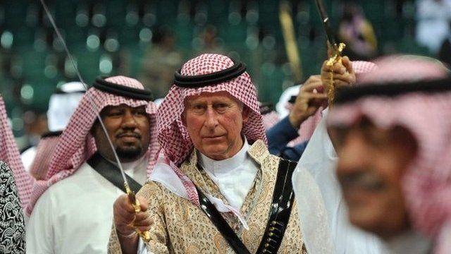 Prince Charles, wearing a traditional Saudi uniform, dances with a sword during traditional Saudi dancing