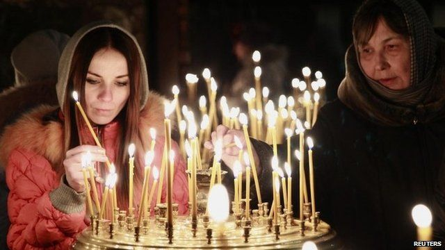 People light candles during a religious service at a church in Kiev