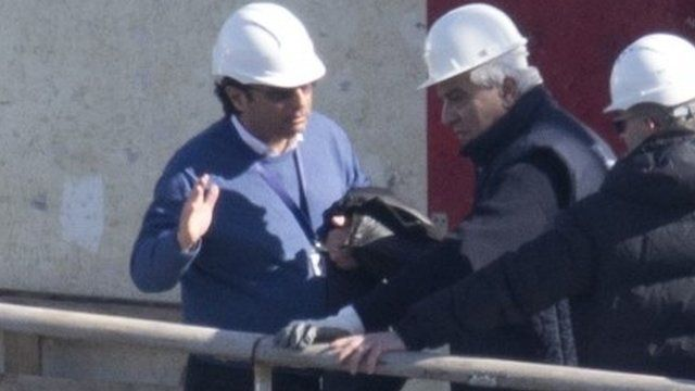 Captain Francesco Schettino, left, talks on the upper deck of the wreck of the Costa Concordia cruise ship
