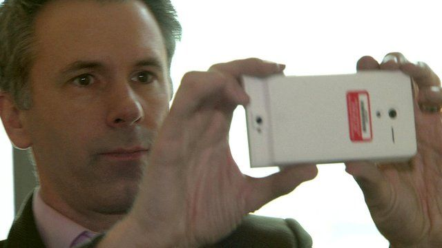 Spencer Kelly holding a Google Project Tango smartphone
