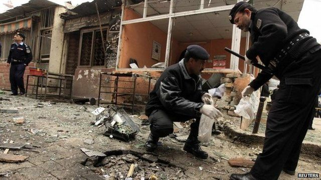 Policemen collect evidence from the site of a bomb attack at the district court in Islamabad March 3, 2014
