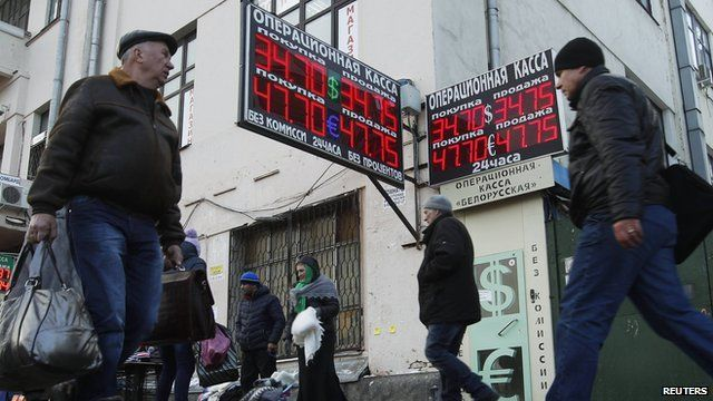 People walk past a currency exchange in Moscow