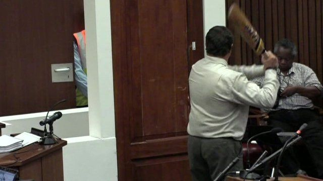 Police Col Vermeulen demonstrates hitting the door with the bat