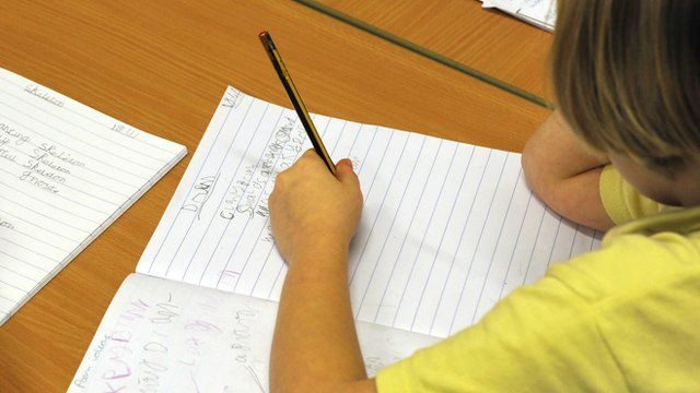 Left-handed child writes in a book