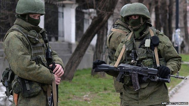 Russian soldiers patrol outside the navy headquarters in Simferopol on March 18, 2014