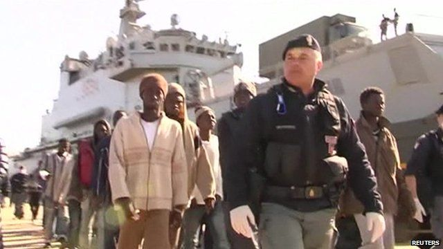 rescued migrants being led away