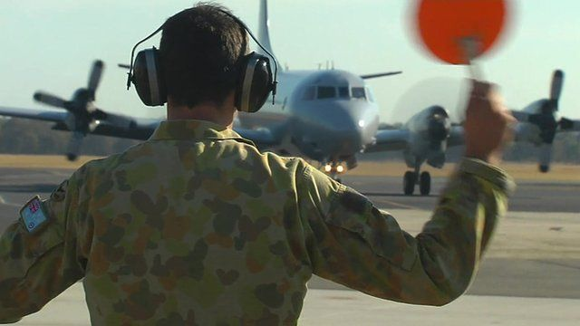 RAAF personnel waving in another search and rescue plane