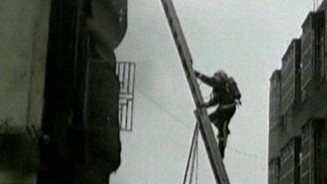 A fireman climbs a ladder outside the factory