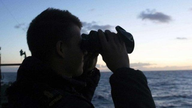 A man searching from aboard an Australian Navy ship