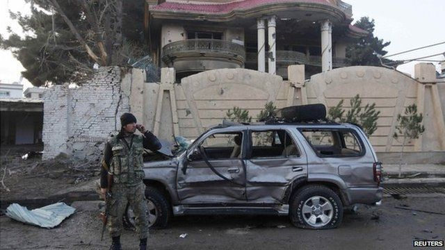 An Afghan security personal stands guard outside a guesthouse, the site of a suicide attack in Kabul on 29 March 2014.