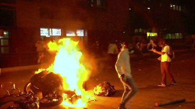Protesters set fire to a police motorcycle