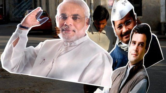 Man holding cardboard cut-outs of Indian election candidates