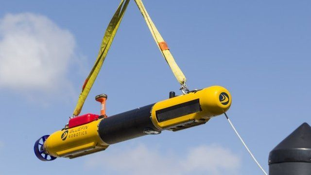 A submarine built by Bluefin Robotics is lowered down onto a boat at their headquarters in Quincy, Mass
