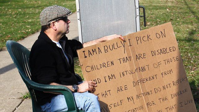 Man holding sign saying 'I am a bully'