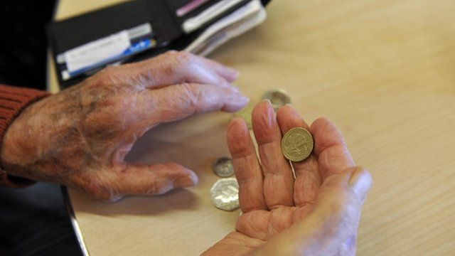 A pensioner with money in her hand
