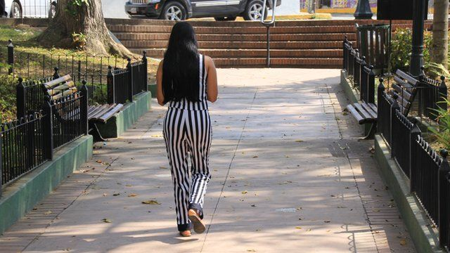 Woman walking away from camera along a path