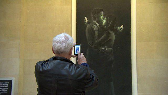 Man takes photo on phone of Banksy art