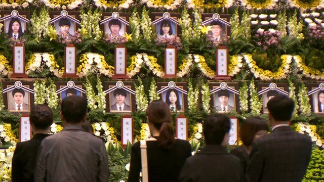Photographs of victims at a memorial service