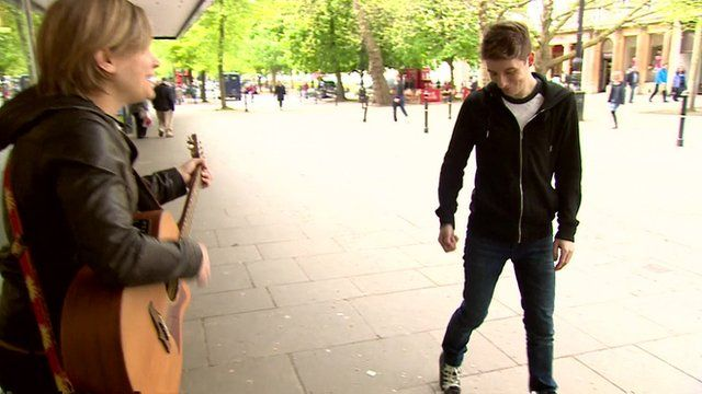 Luke Cameron gives busker money