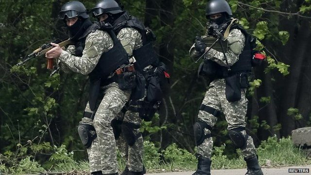 Ukrainian security force officers walk past a checkpoint set on fire and left by pro-Russian separatists near Sloviansk