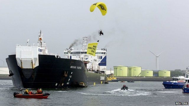 A member of Greenpeace in a hang-glider, carrying a banner over the Russian oil tanker