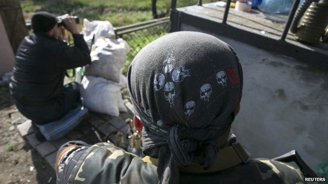 Pro-Russian armed men guard checkpoint