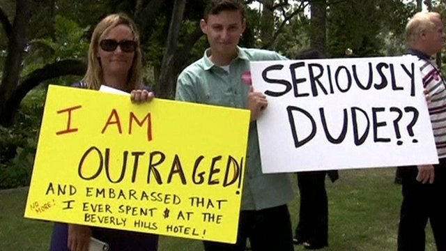 Protestors hold signs outside the Beverley Hills Hotel