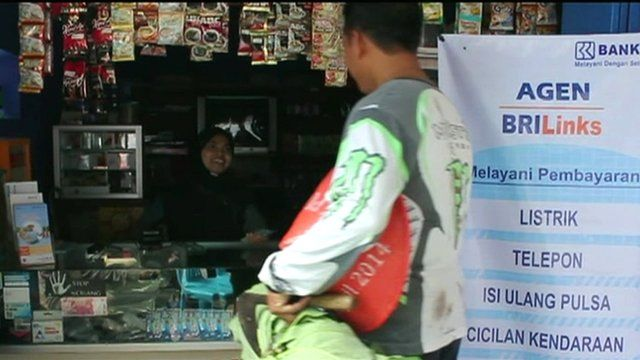 A farmer withdraws money from a bank agent at a local shop in central Java
