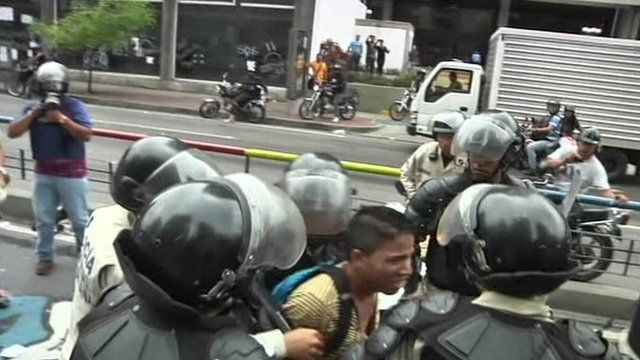 A protester is taken away by the police in Caracas