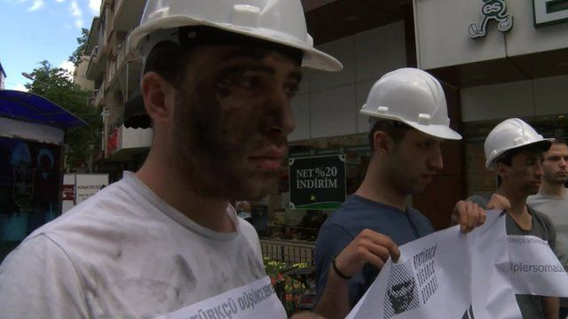 Protesters with faces painted with coal dust