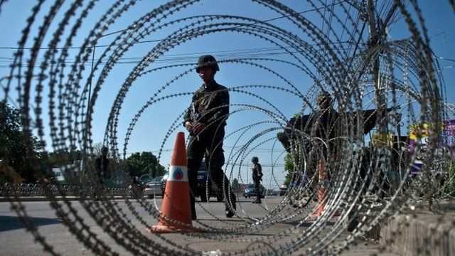 Thai soldiers stand guard at a checkpoint on the outskirts of Bangkok