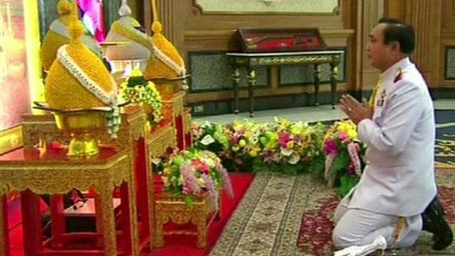 General Prayut Chan-O-Cha paying respects in front of a portrait of Thai King Bhumibol Adulyadej