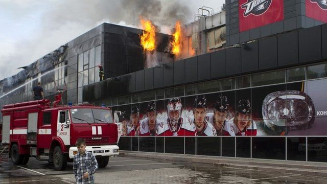 """A boy walks by as firefighters attempt to extinguish a fire at the sports arena Druzhba , which is the home venue of the ice hockey club """"Donbass"""", in Donetsk"""