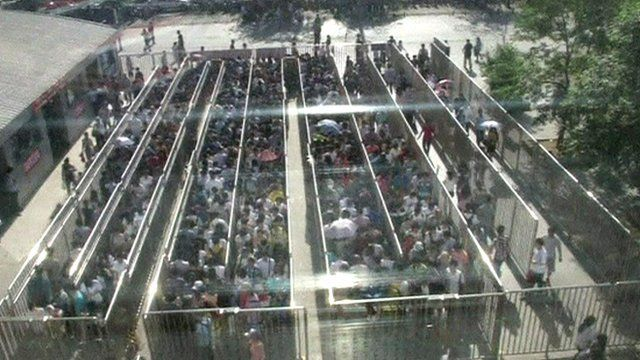Commuters queue at a subway station in Chinese capital Beijing