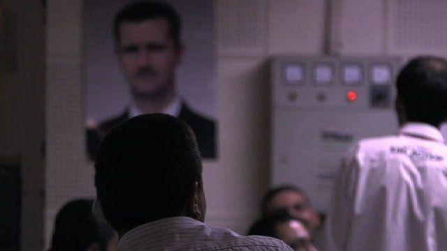 Men's backs with poster of President Assad in background