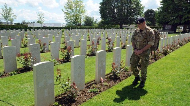 A British soldier looks at graves in the Bayeux War Cemetery