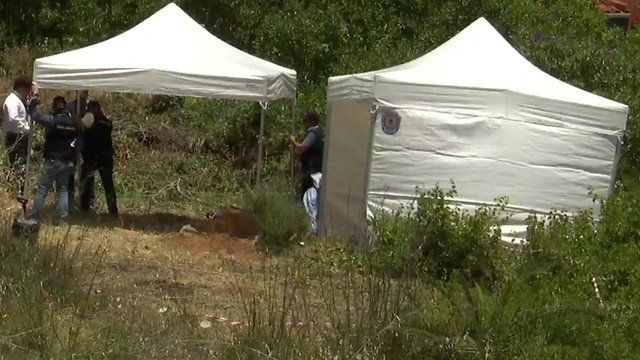 Police officers search an area of scrubland in the Madeleine McCann case