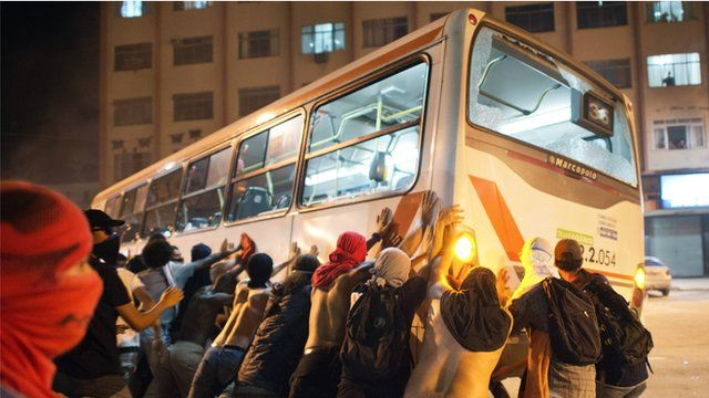 Brazilian protesters pushing over a bus