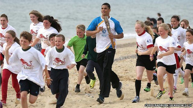 Anthony Ogogo runs with children on Lowestoft beach