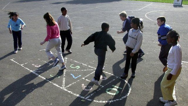 Primary school children playing hopscotch in playground.